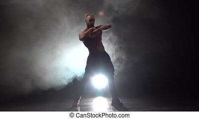 Bearded man is dancing a strip with a bare . Smoke...