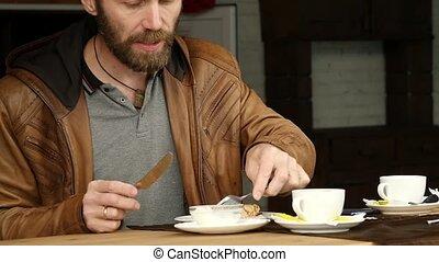 bearded man is having breakfast in the terrace of outdoor...