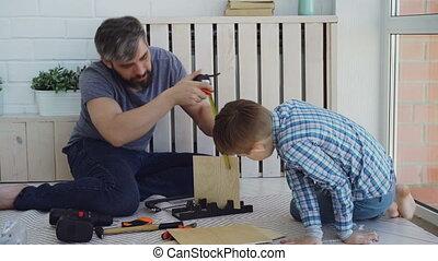 Bearded man is measuring sheet of wood with measure-reel...