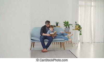 Bearded man is reading book and showing illustrations to his son while relaxing on sofa in light apartment. United family, spending leisure time and raising children concept.