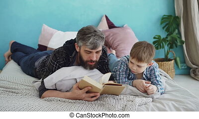 Bearded man is reading book to his little son lying on bed...