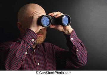 Bearded man looking through binoculars into the distance