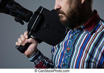 Bearded Man Movie Camera thoughtfully looks aside. cinema...