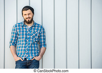 Bearded man - Young bearded man in hat is standing outdoor.