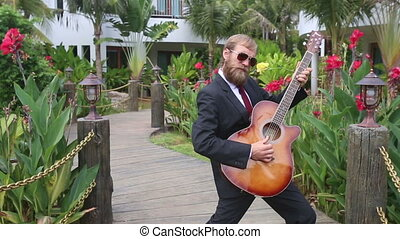 bearded man plays guitar aggressively among flowers