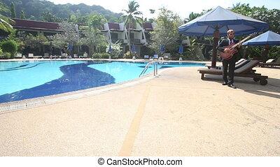 bearded man plays guitar and sings near pool