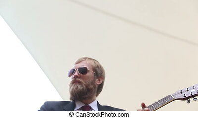 bearded man plays guitar chord and goes out - light haired...