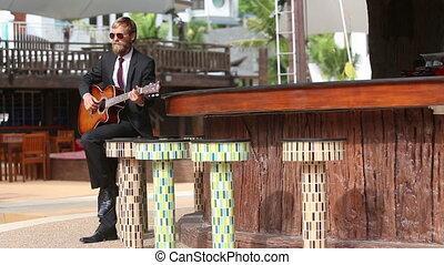 bearded man plays guitar sensually by bar counter -...