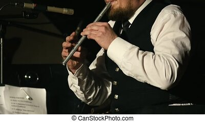 Bearded man plays pipe on the stage, telephoto