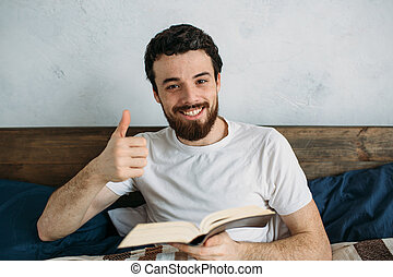 Bearded man reading a big book lying in his bedroom.