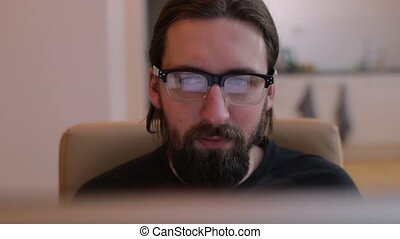 Bearded man reading from monitor close up