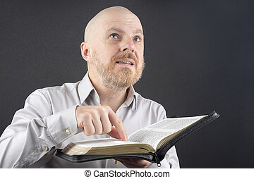 bearded man reading the Bible points his finger at the text and looks up