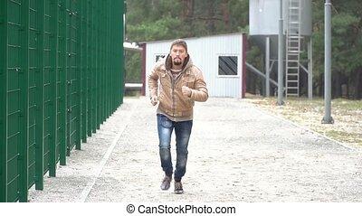 Bearded man runs on the camera