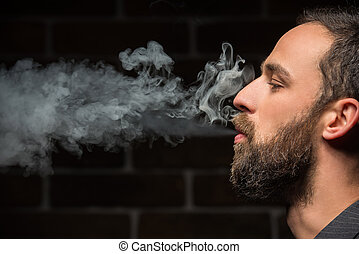 Bearded man - Side view of young bearded man is smoking...