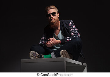 bearded man sits in the studio