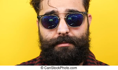 Bearded man smiles on yellow background - Slow motion of...
