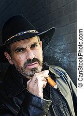 Bearded man smoking cigar - Man with beard in cowboy hat...