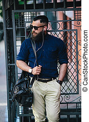 bearded man standing and listening to music