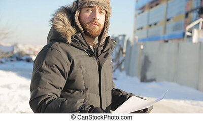 Bearded man stands on cold winter street and keeps plan in his arms.