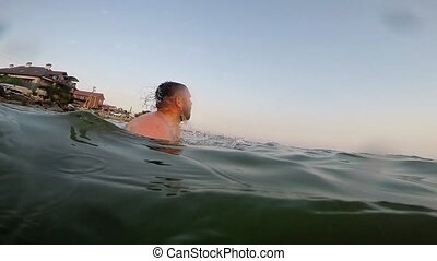 Bearded man swims in the sea