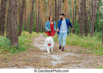 Bearded man taking her wife and dog for a walk in the forest