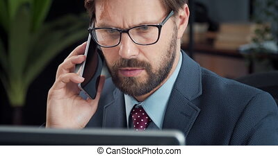 Bearded man talking on mobile and looking at computer screen...