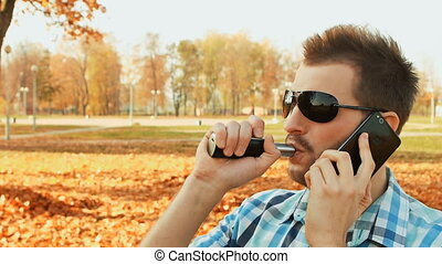 bearded man talking on the smartphone and smoking an...