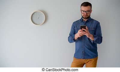 Bearded man using smartphone against a gray wall with a clock