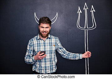 Bearded man using smartphone standing over blackboard background
