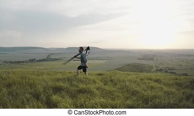 Bearded man walking on hill with tripod and digital camera...