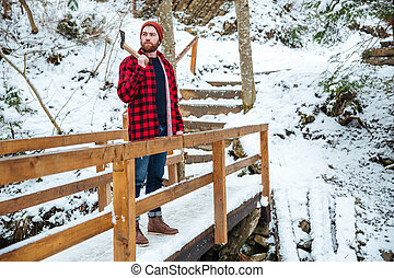 Bearded man with axe standing on wooden bridge in winter