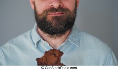 Bearded man with curled up mustache eating chocolate chip cookies on a gray wall background. Close-up