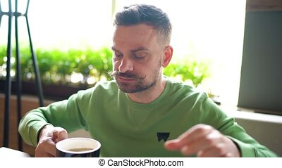 Bearded man with curled up mustache eats chocolate eclair and drinks coffee in cafe. Close-up