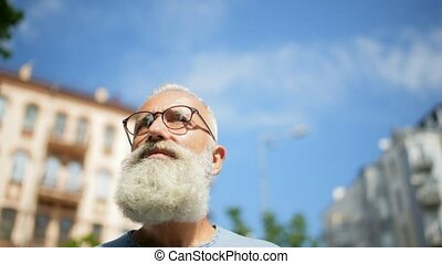 Bearded man with glasses promenading in downtown - Such a...