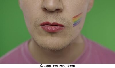 Bearded man with painted lips kiss on the camera. LGBT community. Transsexual