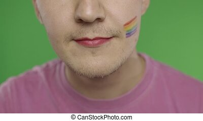 Bearded man with painted lips smiling on the camera. LGBT community. Transsexual