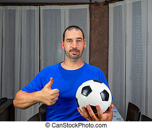 Bearded man with short hair in blue shirt holding a soccer ball with his thumb up