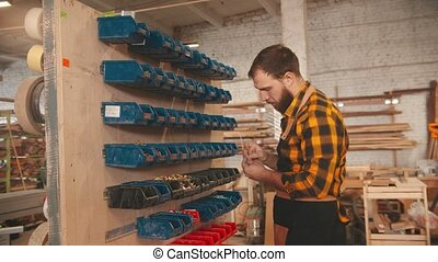Bearded man worker choosing screws from the stand in the carpentry workshop and walks away
