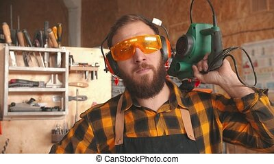 Bearded man worker in yellow shirt and protective glasses standing in the workshop holding grinding instrument