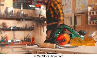 Bearded man worker in yellow shirt choosing instruments in the workshop and takes the headphones from the table
