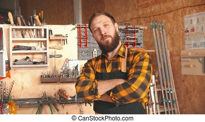 Bearded man worker in yellow shirt standing in the workshop - crossing his hands