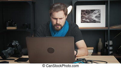 Competent bearded man in black t-shirt and blue scarf sitting at modern studio and working with photographic material on laptop. Concept of creativity and hobby.