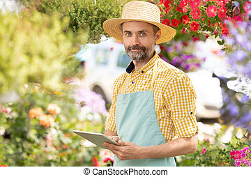 Bearded mature man in apron and hat scrolling in touchpad