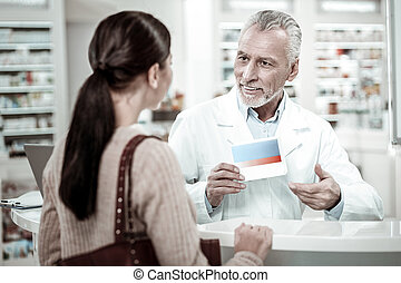 Bearded mature pharmacist holding pill box while providing service his client