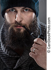 Bearded m??czyna dressed like a sailor. He wears a black cap and a pipe in his mouth.