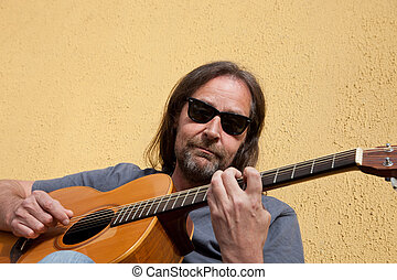 Bearded middle-aged man playing the guitar