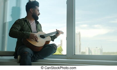 Bearded mixed race guitarist is sitting on windowsill singing playing acoustic guitar at home alone. Beautiful contemporary city is visible in background.