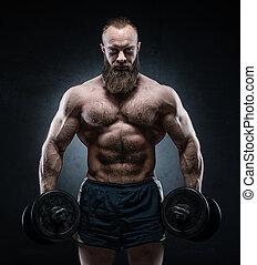 Bearded Muscular bodybuilder posing with heavy dumbbells on...