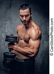 Bearded muscular male l holds dumbbell.