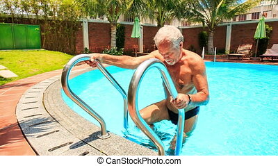 Bearded Old Man Comes out of City Pool by Ladder Closeup -...